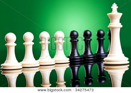 white king in front of pawns of both white and black color chess pieces. leader and his team