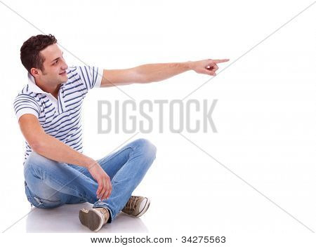 young casual man pointing to his left side on white background