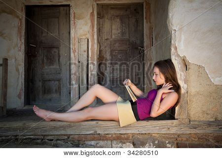 Relaxed young woman reading a book on an old derelict porch