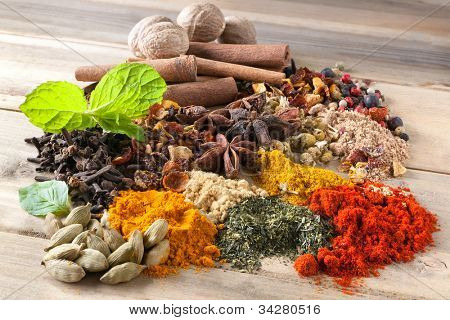 Mixture of beautiful spices and herbs on a wooden table