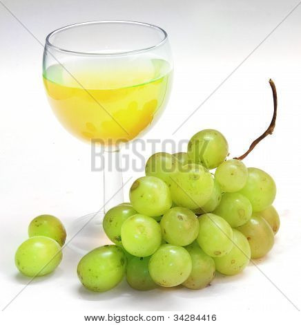 glass glass with juice and green grapes on a white background