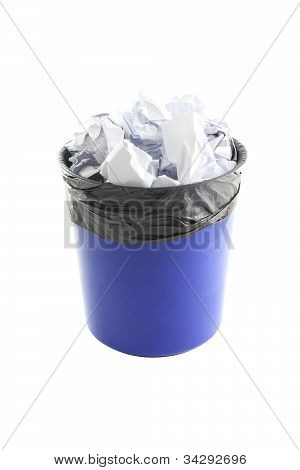 Blue plastic trash and paper in garbage bag on white background.