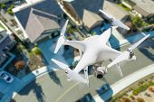 Unmanned Aircraft System Quadcopter Drone In The Air Over Residential Neighborhood. poster