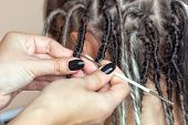 A Hairdresser Weaves Dreadlocks To A Beautiful Young Girl In A Hairdressers. Professional Hair Care poster