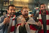 Group of soccer supporters wearing flag scarf and painted face while cheering for sport in bar. Enth poster