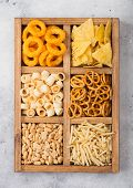 Various Snacks In Vintage Wooden Box On Light Kitchen Background. Onion Rings,nachos, Salty Peanuts  poster