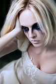 stock photo of moaning  - Beautiful young blond girl dressed like a sad gothic bride - JPG