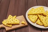 Cheese Crackers, Salty Snack Concept. Cookies, Plate, Cutting Board. Wooden Planks Background, Copy  poster