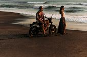 A Couple In Love On The Beach Meets The Sunset. Beautiful Couple On A Motorbike Meets Sunset By The  poster