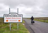 Male Cyclist Entering Northumberland On The Coast To Coast Trail, Uk poster