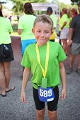 Smiling boy at the finish of a marathon or triathlon wearing a finisher medal poster