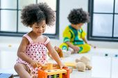 Portrait Of One Young African Mixed Race Girl Is Playing With Toys In Front Of The Other African Boy poster