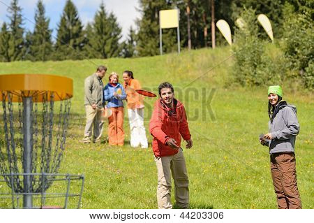 Couple throwing flying disc to chain basket at springtime park