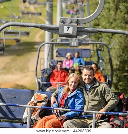 Couple hugging on romantic chairlift trip sunny day