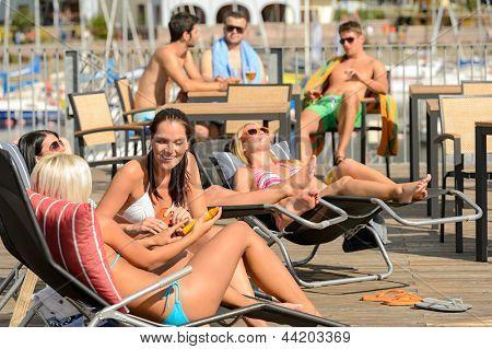 Chatting girls lying on deckchair sunbathing in bikinis sunny day