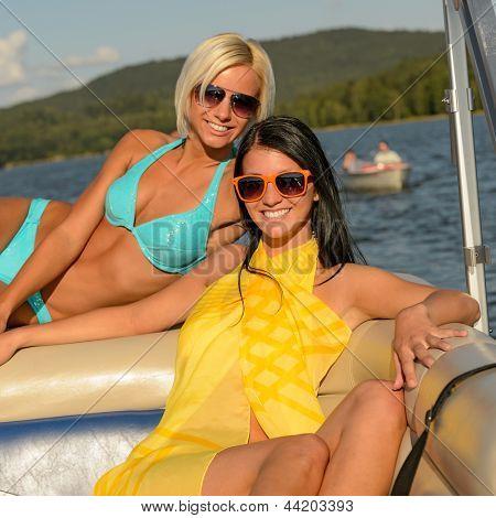 Young happy women sunbathing on boat enjoying summer