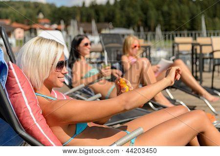 Young women lying on deckchair applying sunscreen in bikini