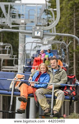 Lovely hiker couple sitting together on chairlift