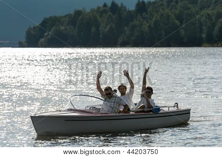 Silhouette of waving young men sitting in motorboat