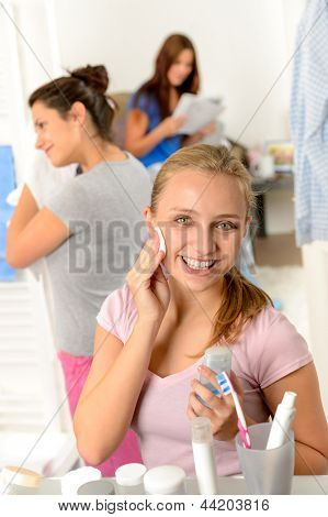 Teenage girl cleaning face with cotton pad with her friends