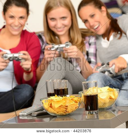 Smiling teenage girls playing with video games with potato chips