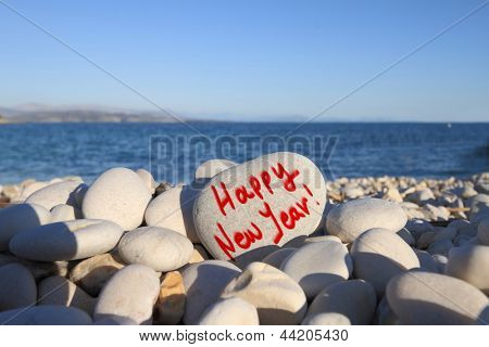 Happy new year written on heart shaped stone on the beach with spray brush