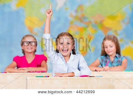 Back to school - elementary school pupil raising hand