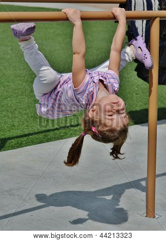 A cute girl playing on bars.