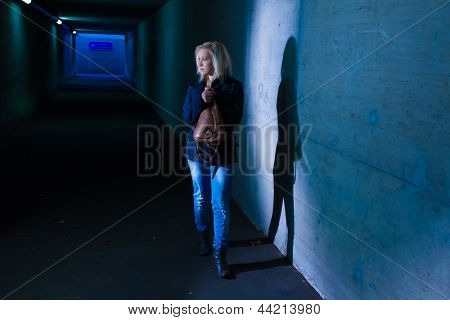 a young woman in an underpass for pedestrians fear of harassment and crime