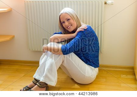 a young woman sits in front of a radiator in winter.