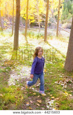 Autumn kid girl running poplar tree forest motion blur in nature outdoor