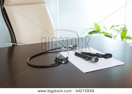 Doctor office table desk and beige chair with stethoscope otoscope and white paper