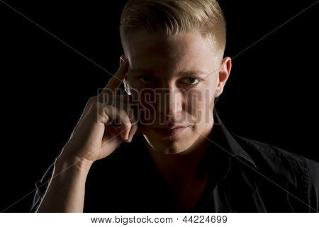 Low-key close up portrait of young serious man in dark shirt looking straight, isolated on black background.