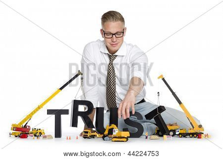 Build up trust concept: Friendly businessman building the word trust along with construction machines, isolated on white background.