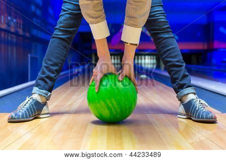 Funny beginner woman aiming to bowling pins