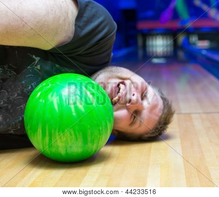 Bizarre drunk man lying on bowling alley