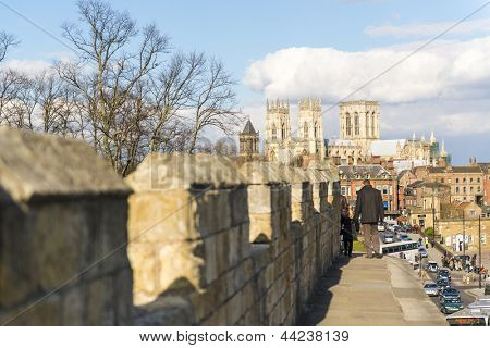 YORK, UK - MARCH 30: Pedestrians walking on the medieval wall that surrounds the city, with York Minster in the background. March 30, 2013 in York.
