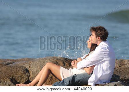 Casal abraçando e vendo o mar