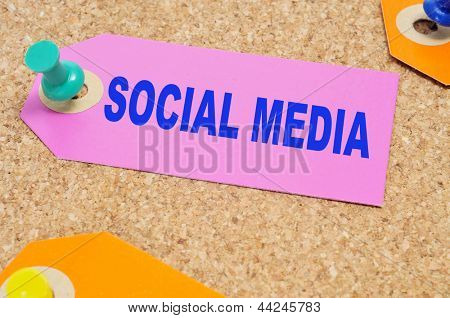 a paper label with the words social media written on it, pinned with a thumb tack on a cork board