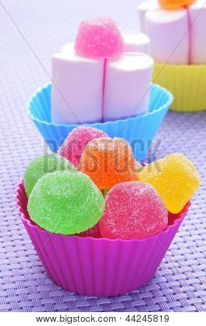 gumdrops of different colors and marshmallows in bowls of different colors on a purple woven background