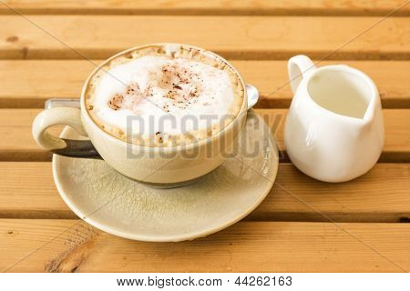 A Cup Of Coffee Latte On A Wooden Table In An Cafe.
