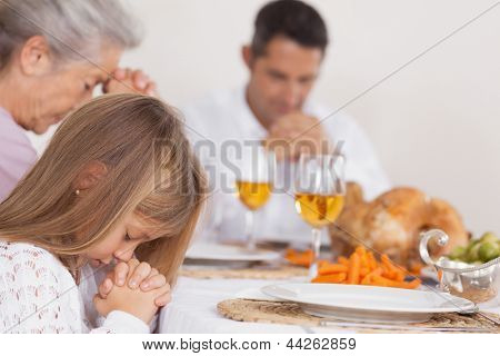 Little girl saying grace with family before thanksgiving dinner