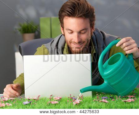 Homem molhar flores cor de rosa na mesa de Primavera em casa, computador portátil na mesa.