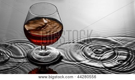 Cognac in glass on water ripples background
