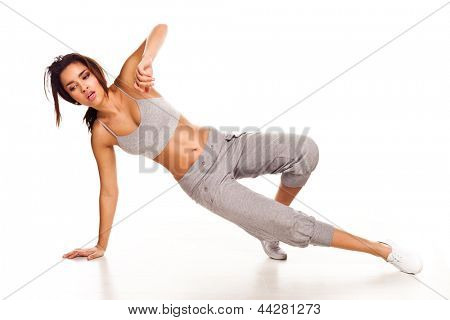 Beautiful athletic young hip hop dance performing against a white studio background balanced gracefully on one arm and the tips of her toes