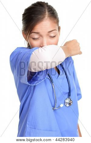 Sneezing woman medical nurse or doctor doing elbow sneeze being sick having the cold flu. Sneezing instruction concept with person in medical scrubs. Young female isolated on white background