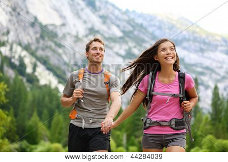 Happy couple of hikers hiking holding hands joyful, cheerful and fresh. Young active multiracial couple in outdoor activity hike in Yosemite National Park, California, USA. Asian woman, Caucasian man.