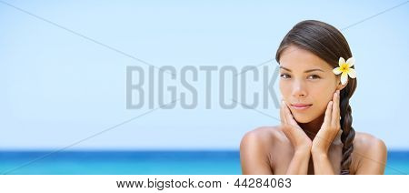 Spa woman on travel beach resort with perfect skin for beauty skin care. Beautiful mixed race Caucasian Asian ethnic girl looking serene a camera during holidays vacation. Panoramic banner on beach.
