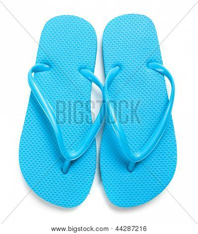 A pair of light blue flipflops on a white background