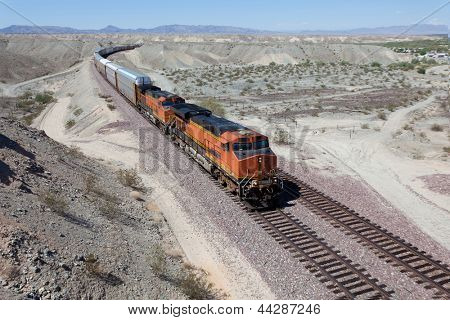 Speeding train cars on a railroad track in the dessert